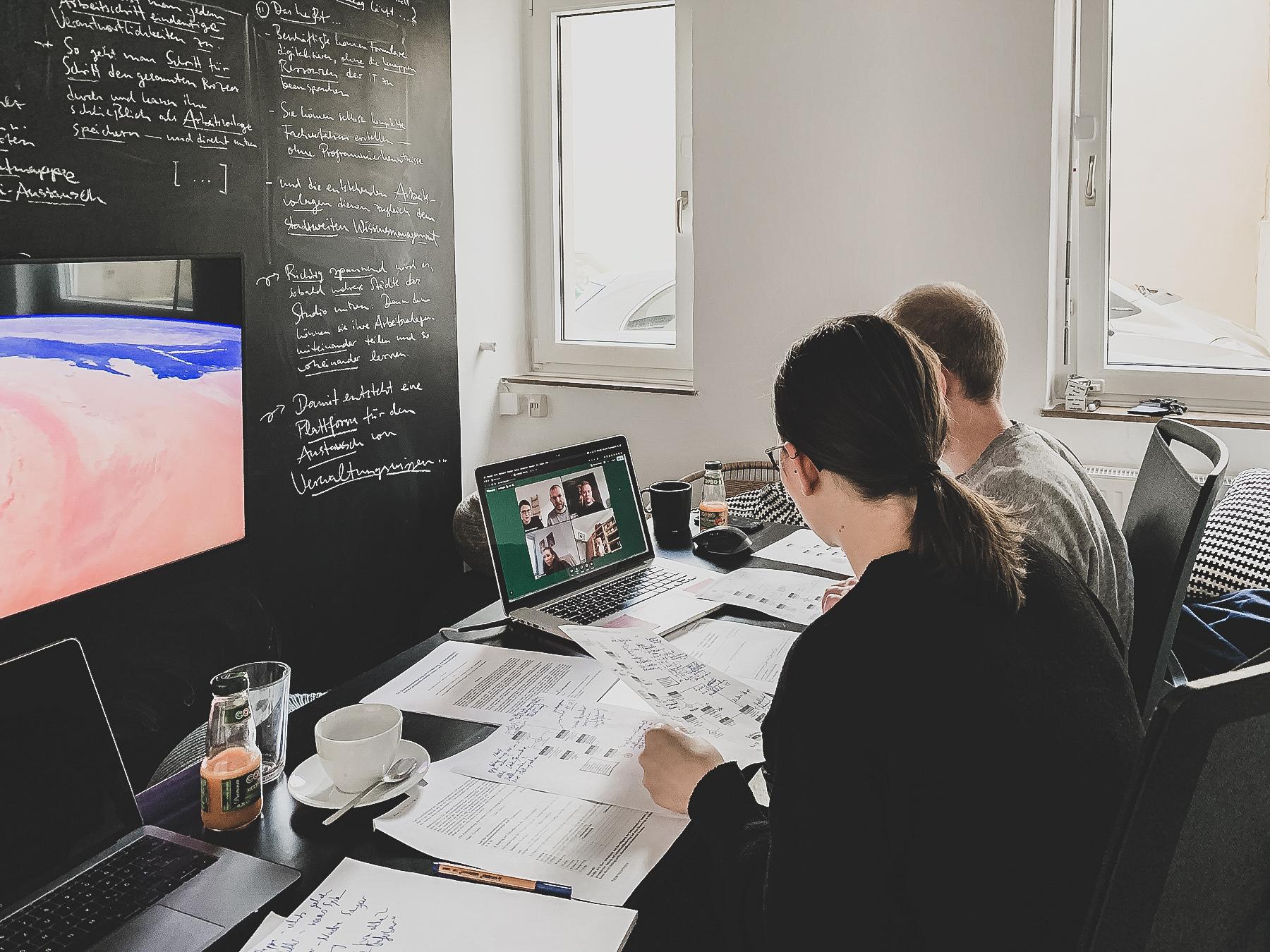 Zwei Leute sitzen arbeitend am Schreibtisch
